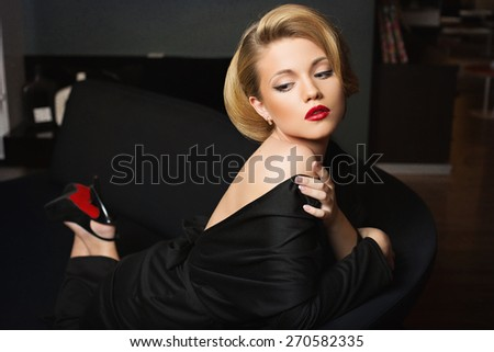 Beautiful young woman in black evening dress lying on sofa - stock photo