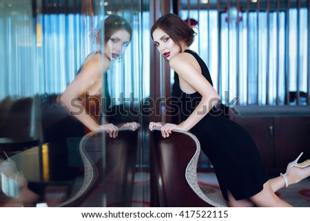 Beautiful young woman in black evening dress posing in interior. - stock photo