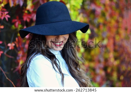 Beautiful young woman in black hat against autumn leaves  - stock photo