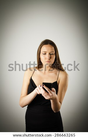 Beautiful young woman in black is using a mobile phone. Young woman is doing something. - stock photo