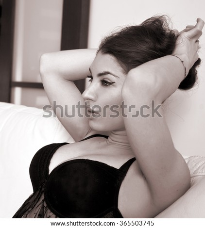 beautiful young woman in black lingerie in the bedroom interior