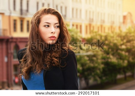 Beautiful young woman in black suit with long luxuriant hair. City style.