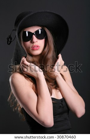 beautiful young woman in black sunglasses and stylish hat
