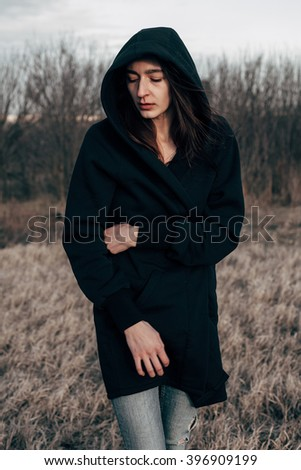Beautiful young woman in black walking outdoors. depressed mood