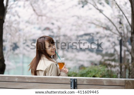 beautiful young woman in blooming cherry blossoms - stock photo