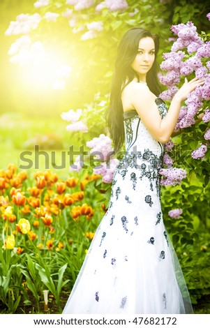 Beautiful young woman in blooming sunny garden - stock photo
