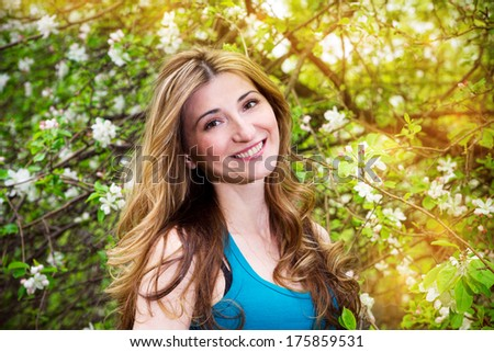 Beautiful young woman in blossoming garden. - stock photo