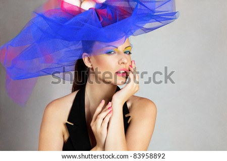 Beautiful young woman in blue fashionable hat touching face - stock photo