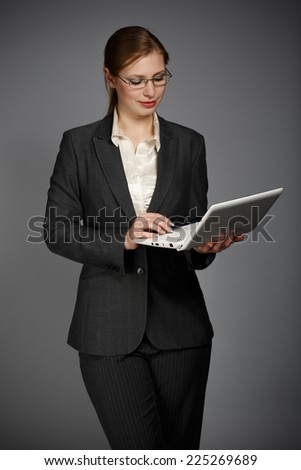 Beautiful young woman in business suit and shirt holding white notebook or pad on grey background