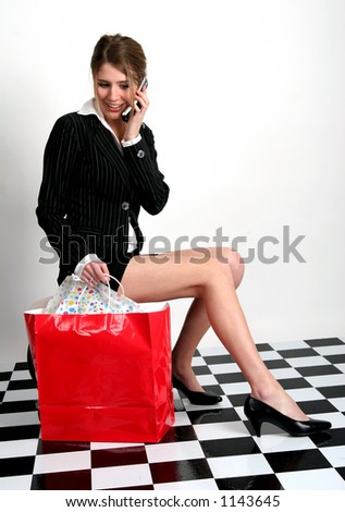 Beautiful young woman in business suit talking on cell phone with red shopping bag next to her.  Young woman talking on the cellphone while sitting with a red bag next to her - stock photo