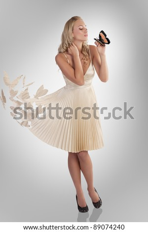 beautiful young woman in butterfly dress holding a and kissing the same insect - stock photo