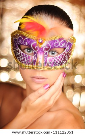 Beautiful young woman in carnival mask - stock photo