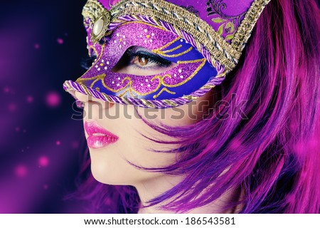 Beautiful young woman in carnival mask. Masquerade. Black background.