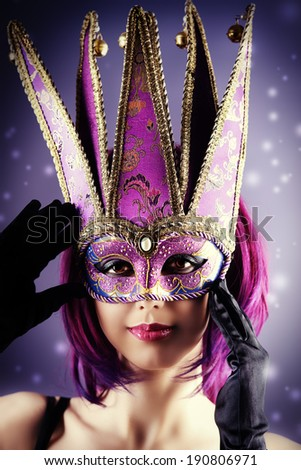 Beautiful young woman in carnival mask. Masquerade. Dark background. - stock photo
