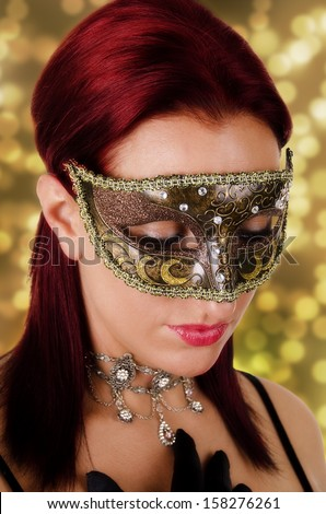 Beautiful young woman in carnival mask, on a bokeh effect background.