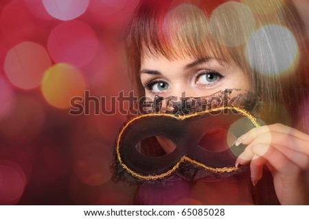 Beautiful young woman in carnival mask over blurred background - stock photo