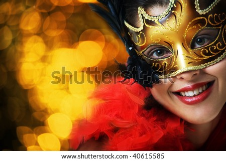 Beautiful young woman in carnival mask over gold background - stock photo