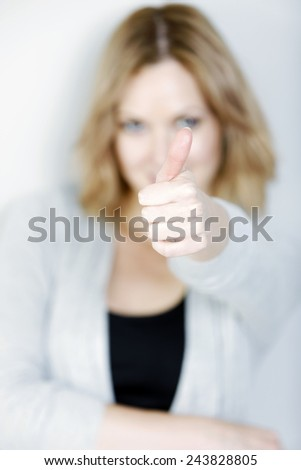 Beautiful young woman in casual blue top holding her thumb up displaying success - stock photo