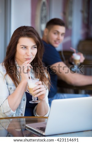 Beautiful young woman in casual clothes sitting in street cafe with laptop and drink, playfully smiling aware of handsome guy looking at her with admiration from the next table