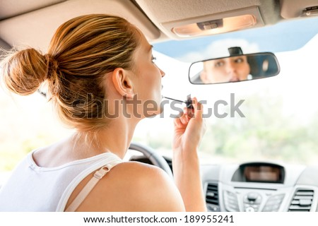 Beautiful young woman in casual summer clothing applying makeup in the car using the rear view mirror to apply red lip gloss as she refreshes her appearance - stock photo
