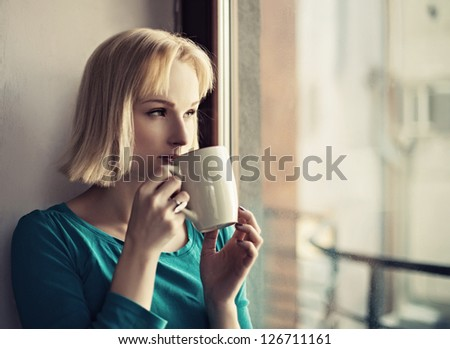Beautiful young woman in casual wear dreaming with cup of hot coffee or tea over window - stock photo