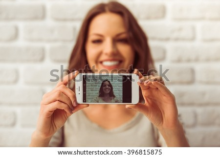 Beautiful young woman in casual wear is making a selfie using a smart phone and smiling, against white brick wall