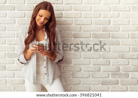 Beautiful young woman in casual wear is using a smart phone and smiling, against white brick wall - stock photo