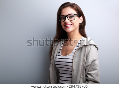 Beautiful young woman in casual wear with toothy smile on blue background with empty copy space - stock photo