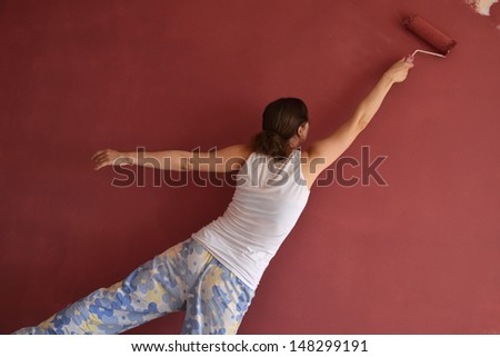 Beautiful young woman in causal clothes having fun and dancing whilst painting a wall with red paint and a roller - stock photo