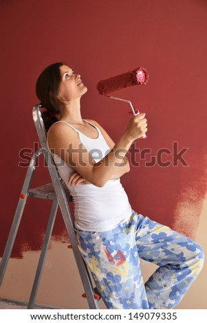 Beautiful young woman in causal clothes taking a break and enjoying the result of the work she has done painting a wall - stock photo
