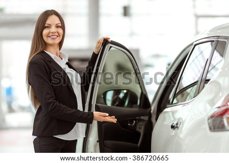 Beautiful young woman in classic suit is smiling and looking at camera while presenting a car in a motor show