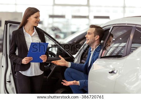 Beautiful young woman in classic suit is smiling while showing a car in a motor show. Handsome young customer is sitting in car