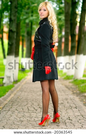 Beautiful young woman in coat and red gloves has looked back in park.