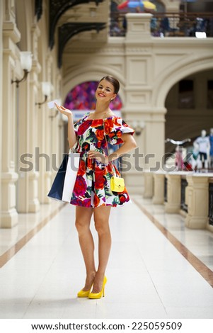 Beautiful young woman in color flowers dress walking in the shop  - stock photo
