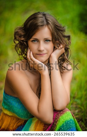 Beautiful young woman in colorful dress sitting on grass, against green of summer park. - stock photo