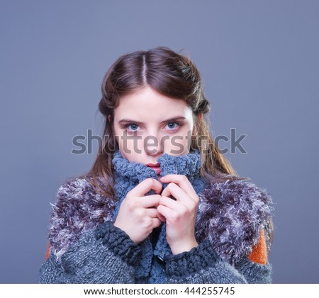 Beautiful young woman in colorful winter outfit. Studio shot.