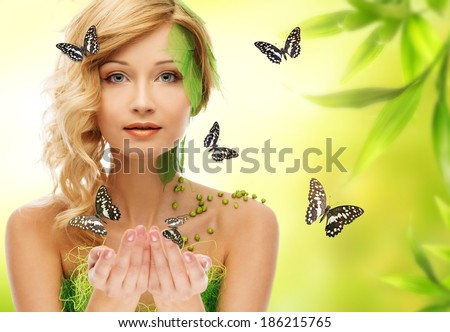 Beautiful young woman in conceptual spring costume with butterflies around her - stock photo