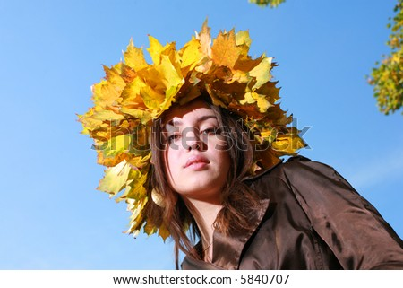 Beautiful young woman in crown of golden autumn leaves, blue sky behind. - stock photo