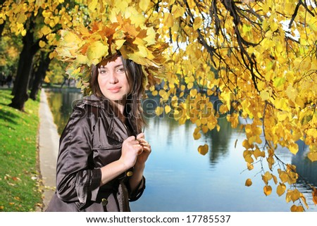 Beautiful young woman in crown of golden autumn leaves in park. - stock photo