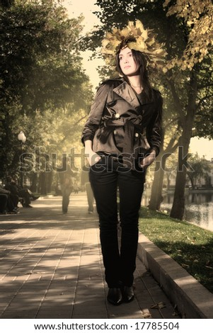 Beautiful young woman in crown of golden autumn leaves in park. Toned in sepia. - stock photo