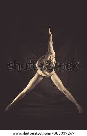 Beautiful young woman in dancing silhouette pose on dark background