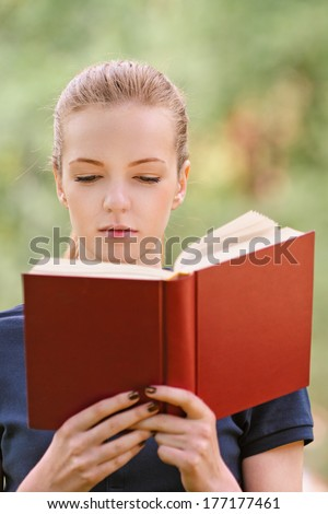 Beautiful young woman in dark blouse reads red book, against green of summer park. - stock photo