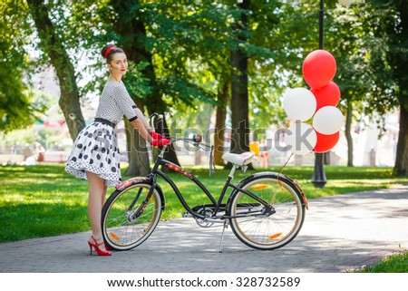 Beautiful young woman in dress retro pin-up style having rest in summer park near her stylish lady city bicycle decorated with red and white balloons. - stock photo