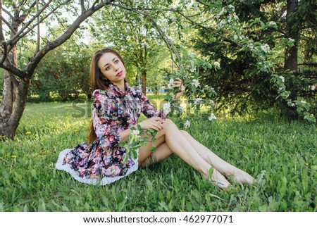 Beautiful young woman in dress sitting under the blooming apple tree.