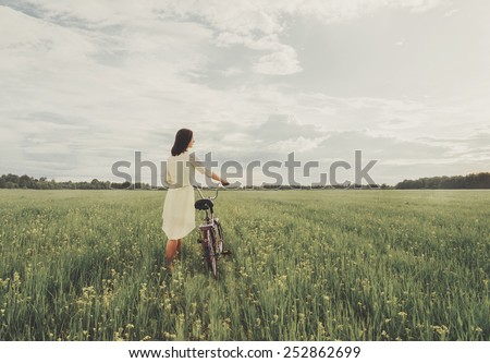 Beautiful young woman in dress walking with a bicycle on summer wildflower meadow. Used filters instagram color. - stock photo