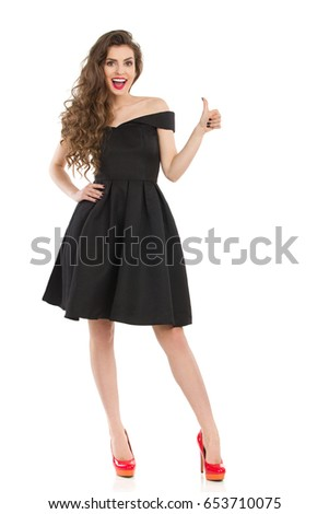 Beautiful young woman in elegant black cocktail dress and red high heels is standing, showing thumb up and smiling. Front view. Full length studio shot on isolated on white.