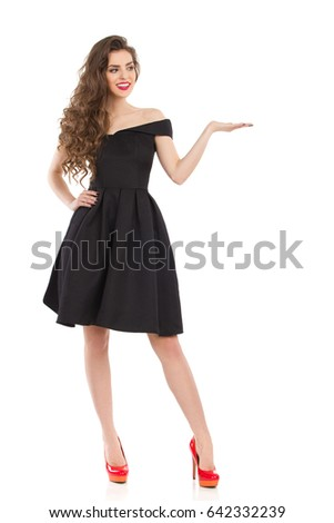 Beautiful young woman in elegant black cocktail dress and red high heels is standing with hand raised, presenting something and looking away. Front view. Full length studio shot on isolated on white.
