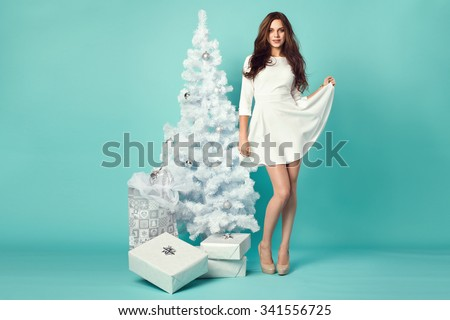 beautiful young woman in elegant dress standing next to white christmas tree and presents. turquoise background - stock photo