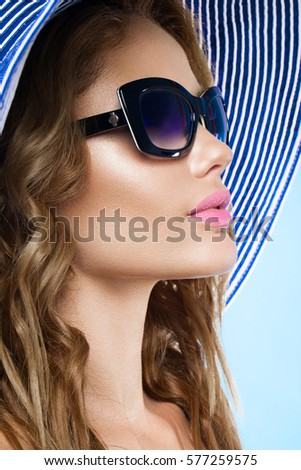 Beautiful young woman in elegant hat and sunglasses.
