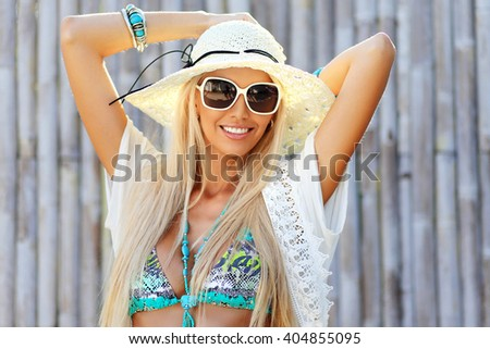 Beautiful young woman in elegant hat and sunglasses posing outdoor - stock photo